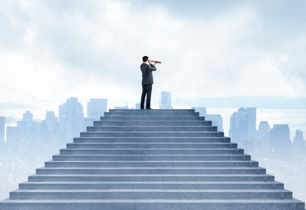 Geschäftsfrau an Spitze der Treppe sieht in Ferne durch ein Fernglas in Richtung Stadt unten – Foto