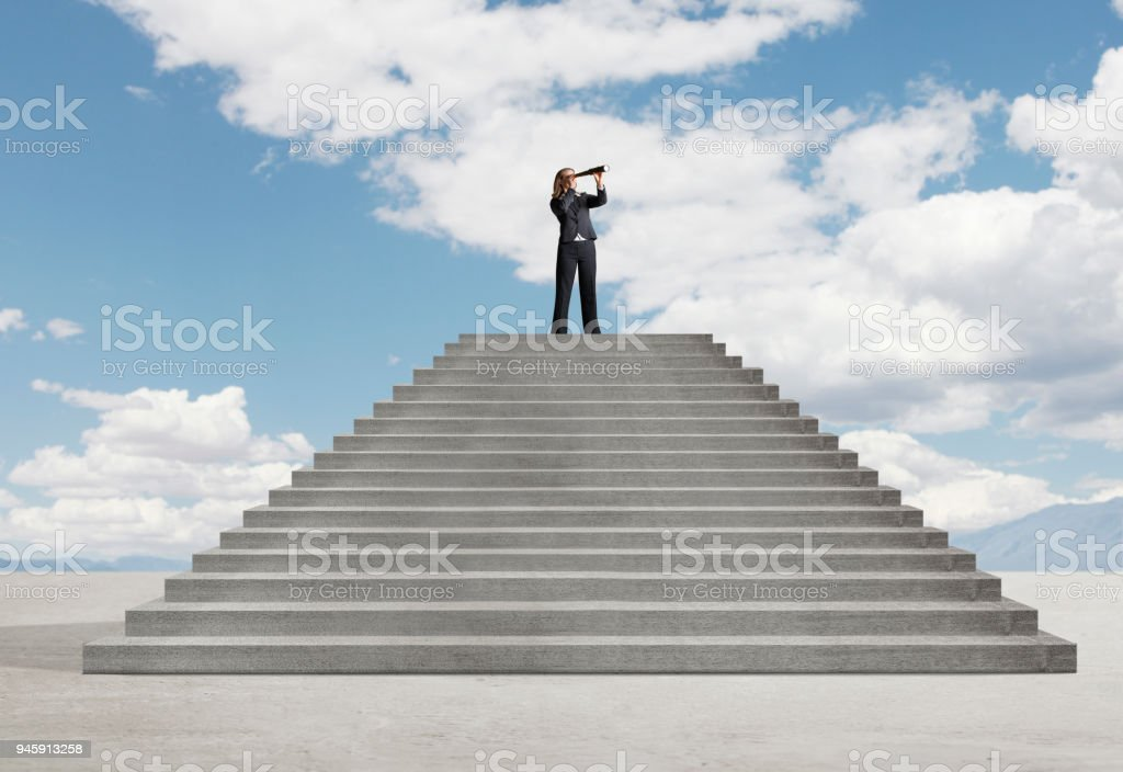 Businesswoman At Top Of Stairs Looks Into Distance Through A