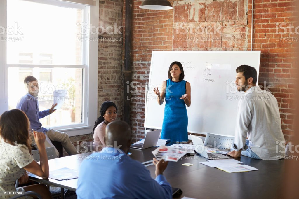 Businesswoman At Whiteboard In Brainstorming Meeting stock photo