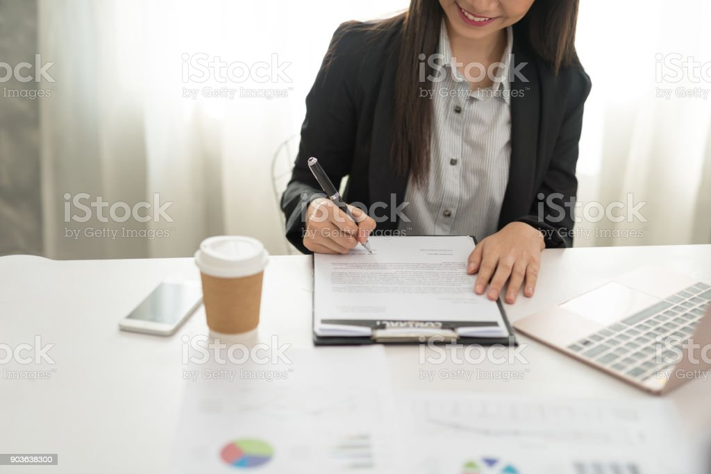Businesswoman at work signing a contract paper in her workstation stock photo