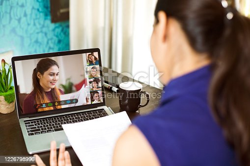 Businesswoman attending business video call meeting on laptop at home