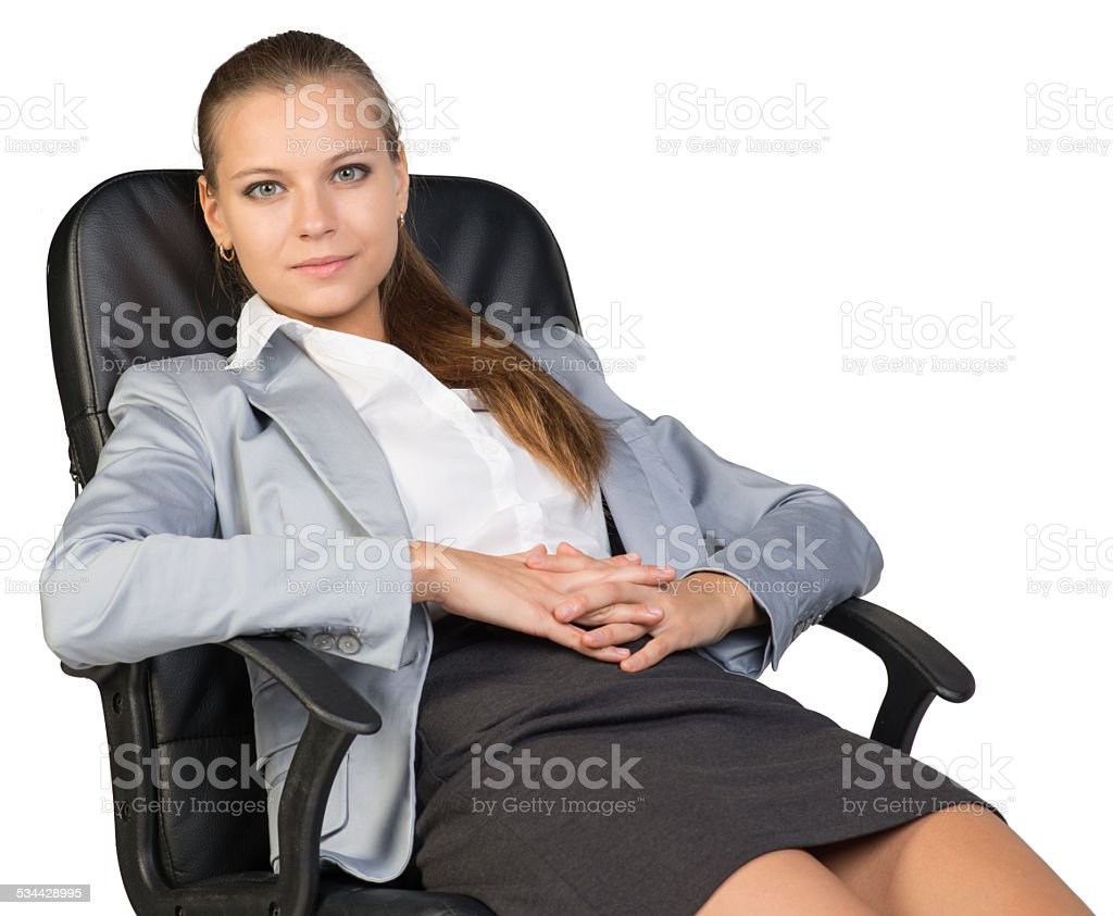 Businesswoman back in office chair, with hands clasped over her stock photo