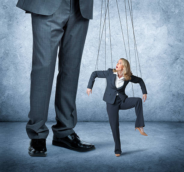 Businesswoman Being Controlled Like A Marionette A large businessman controls the movement of a businesswoman as she is controlled by the strings of a marionette. puppet stock pictures, royalty-free photos & images