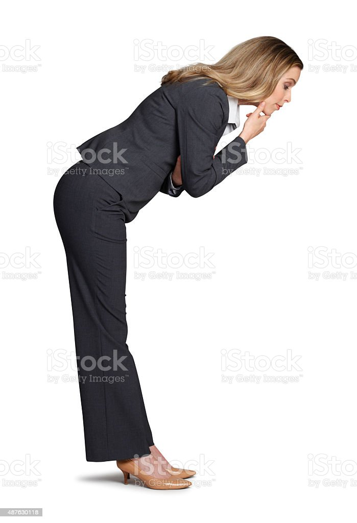 Businesswoman Bending Over And Looking Into The Unknown stock photo