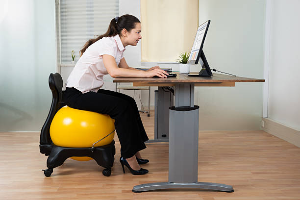 Businesswoman Bending While Sitting On Fitness Ball Businesswoman Bending In Front Of Computer While Sitting On Fitness Ball In Office bad posture stock pictures, royalty-free photos & images