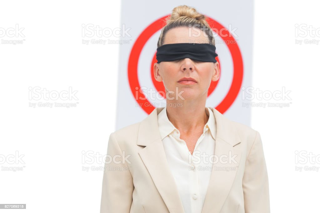 Businesswoman blindfolded and target behind stock photo