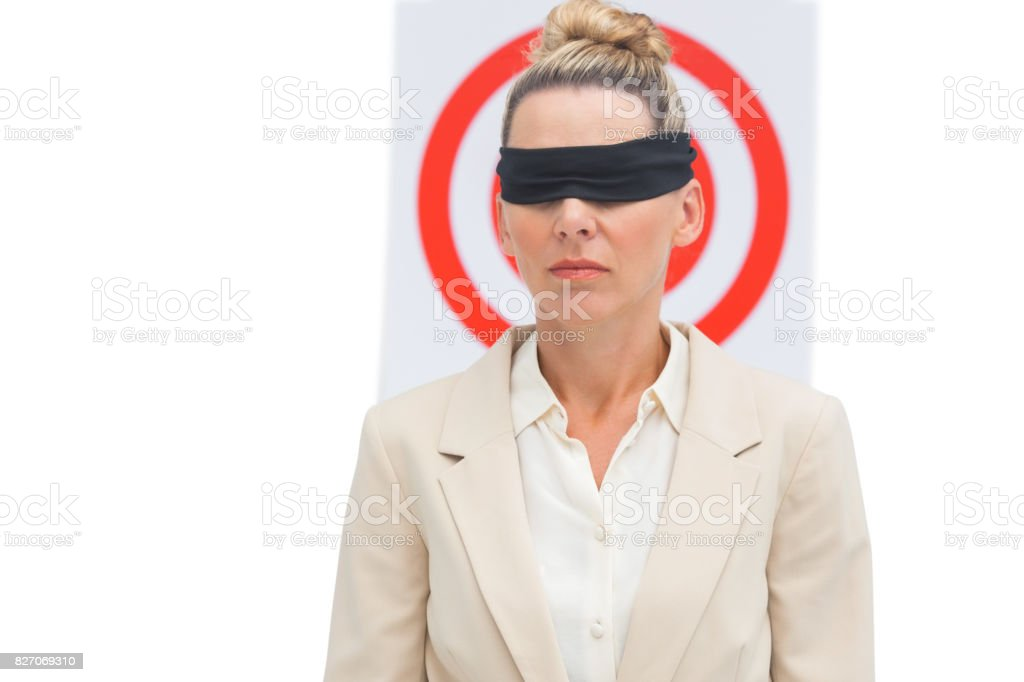 Businesswoman blindfolded in front of target stock photo