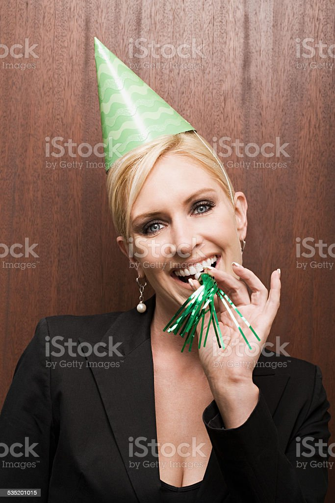 Businesswoman blowing party horn blower stock photo