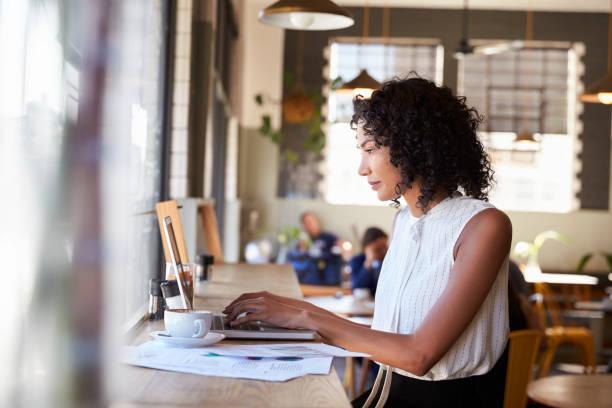 geschäftsfrau fenster arbeiten am laptop in coffee-shop - coffee shop stock-fotos und bilder