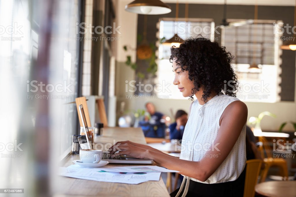 Businesswoman By Window Working On Laptop In Coffee Shop stock photo