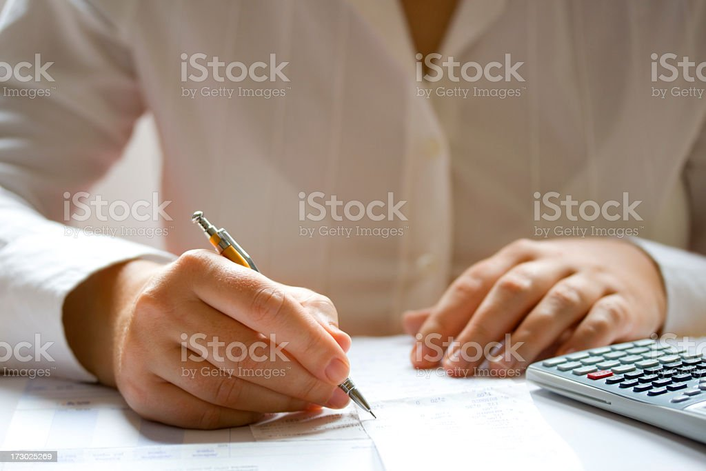 Businesswoman calculating data using a calculator and pen royalty-free stock photo