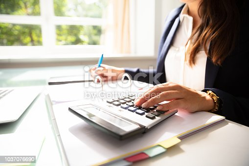 Businesswoman's Hand Calculating Invoice With Calculator In Office