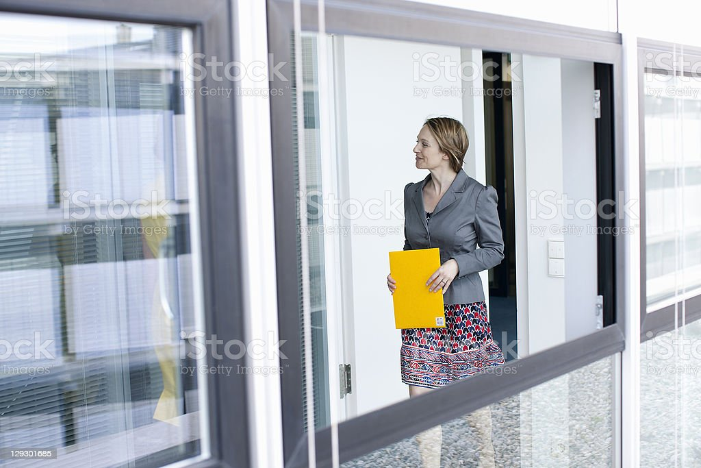 Businesswoman carrying folder in office royalty-free stock photo