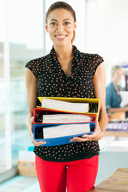 Businesswoman carrying folders stock photo