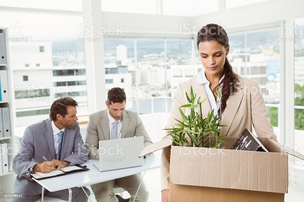 Businesswoman carrying her belongings in box stock photo