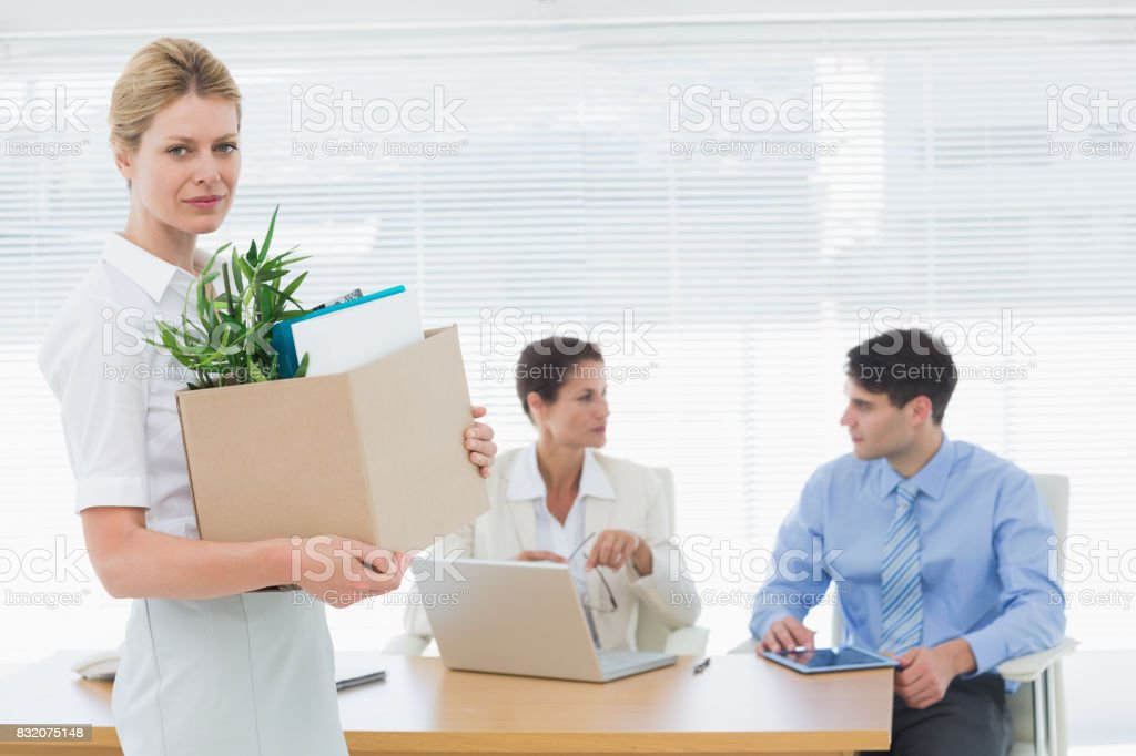 Businesswoman carrying her belongings with colleagues in background stock photo
