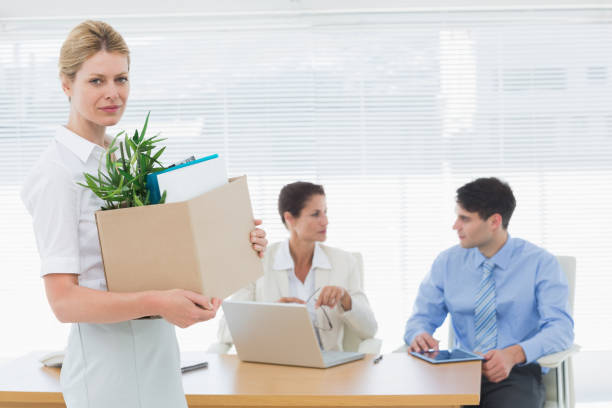 businesswoman carrying her belongings with colleagues in background - leaving partnership corporate business sitting stock photos and pictures