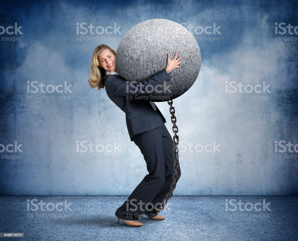 Businesswoman Carrying Large Ball And Chain stock photo