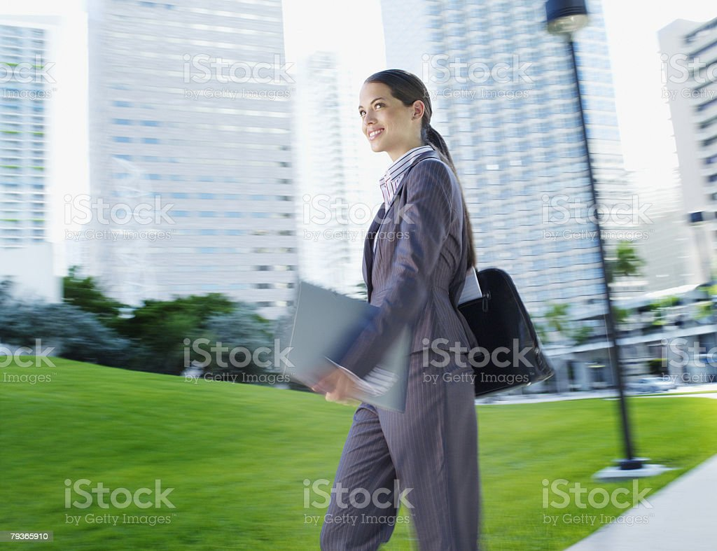 Businesswoman carrying paperwork on path outdoors royalty-free stock photo