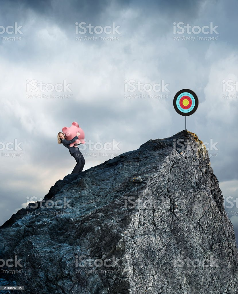 Businesswoman Carrying Piggy Bank Up Mountain To Reach Financial Goals stock photo