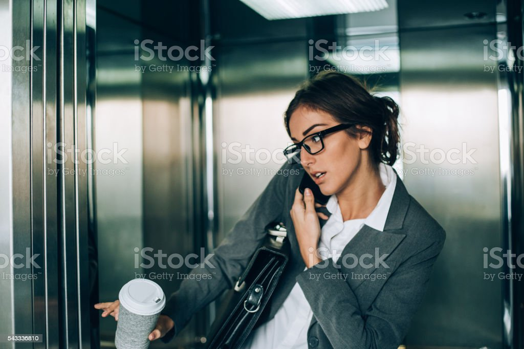Businesswoman catching the elevator stock photo