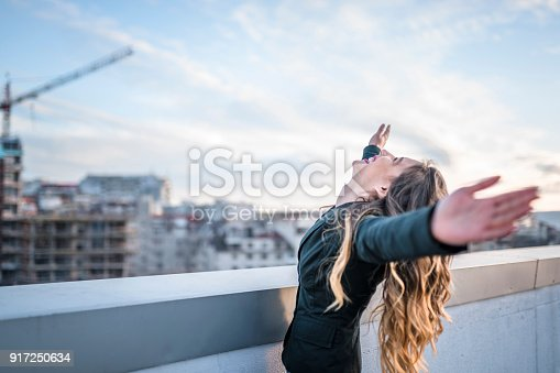 istock Businesswoman celebrating on urban rooftop 917250634
