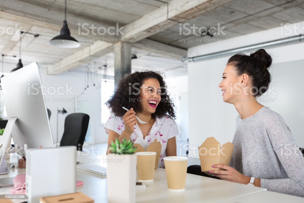 Businesswoman chatting while having lunch at work Two happy young woman sitting at the desk chatting while having lunch. Cheerful young female coworkers taking lunch together at their desk. 20-24 Years Stock Photo