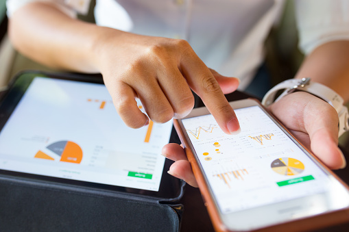 Businesswoman check data in smartphone and tablet