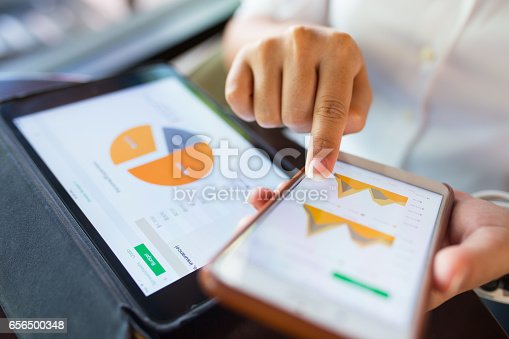 istock Businesswoman check data in smartphone and tablet 656500348