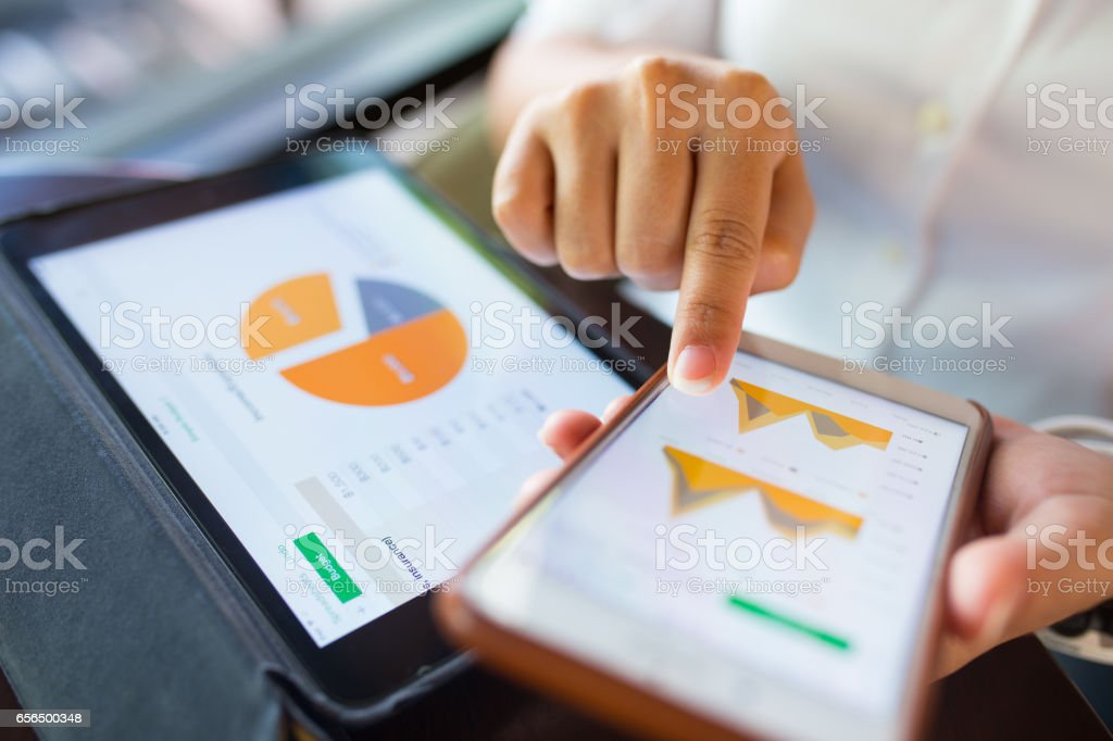 Businesswoman check data in smartphone and tablet stock photo