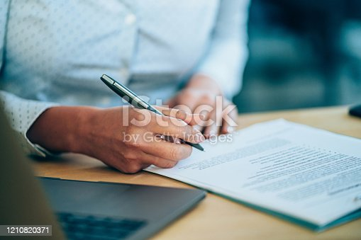 Close-up shot of a businesswoman holding a pen and signing contract.