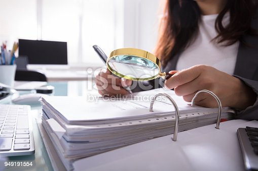 istock Businesswoman Checking Bill Through Magnifying Glass 949191554