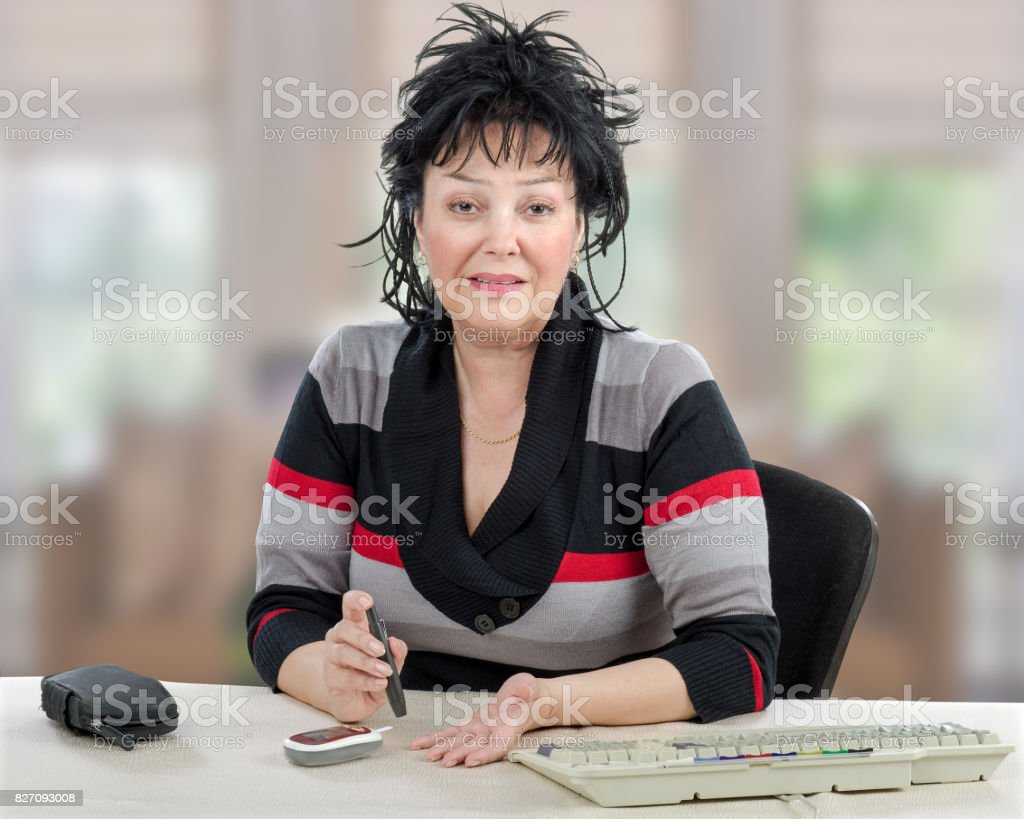 Businesswoman checking blood sugar level stock photo