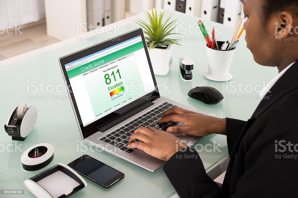 Businesswoman Checking Credit Score On Laptop stock photo