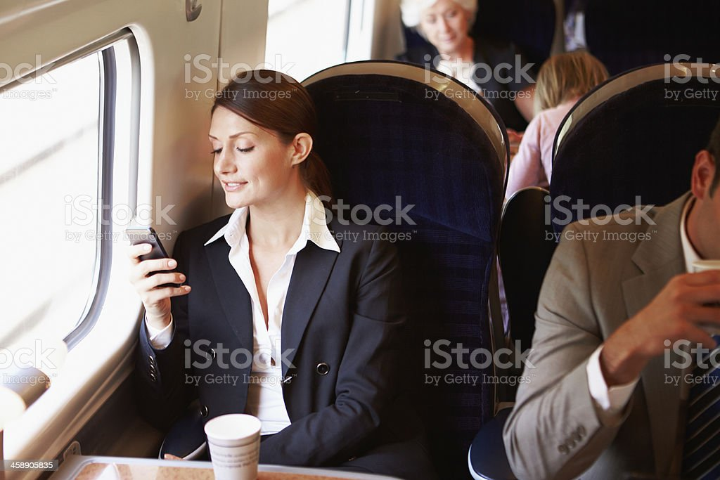 A businesswoman checking her mobile phone while commuting royalty-free stock photo