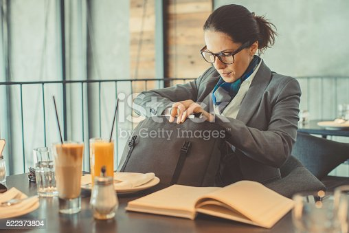 Elegant businesswoman sitting in restaurant and checking her purse