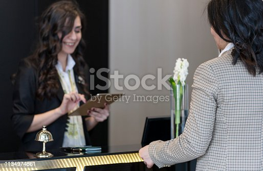 istock Businesswoman Checking In At Hotel Reception 1134974861