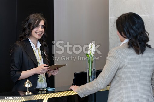 istock Businesswoman Checking In At Hotel Reception 1134974877