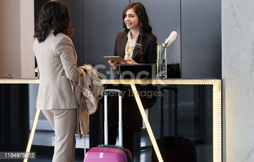 istock Businesswoman Checking In At Hotel Reception 1134975012