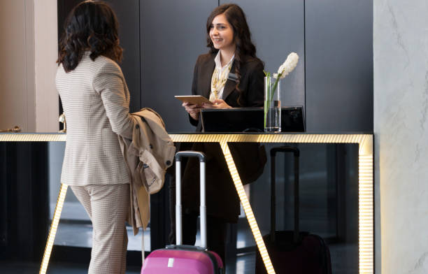 businesswoman checking in at hotel reception - airport check in counter stock pictures, royalty-free photos & images