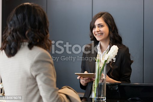 istock Businesswoman Checking In At Hotel Reception 1134975075