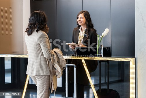 istock Businesswoman Checking In At Hotel Reception 1134975506