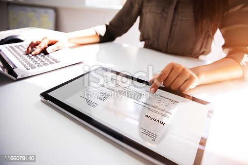 Close-up Of A Busineswoman's Hand Working With Invoice On Digital Tablet