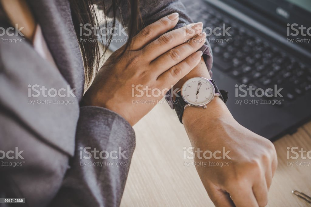 businesswoman checking the time on watch stock photo