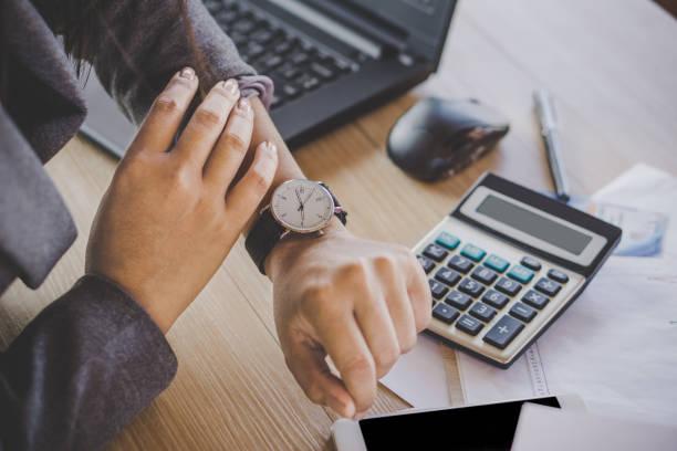 bizneswoman sprawdzanie czasu na zegarek - czas zdjęcia i obrazy z banku zdjęć