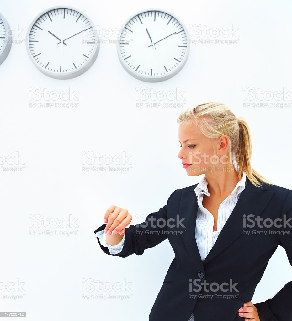 Businesswoman checking time in front of a wall with clocks stock photo