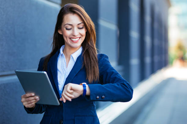 Businesswoman checking time on wristwatch outdoors stock photo