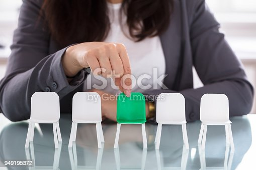 Close-up Of A Businesswoman's Hand Choosing Green Chair Among White Chairs In A Row