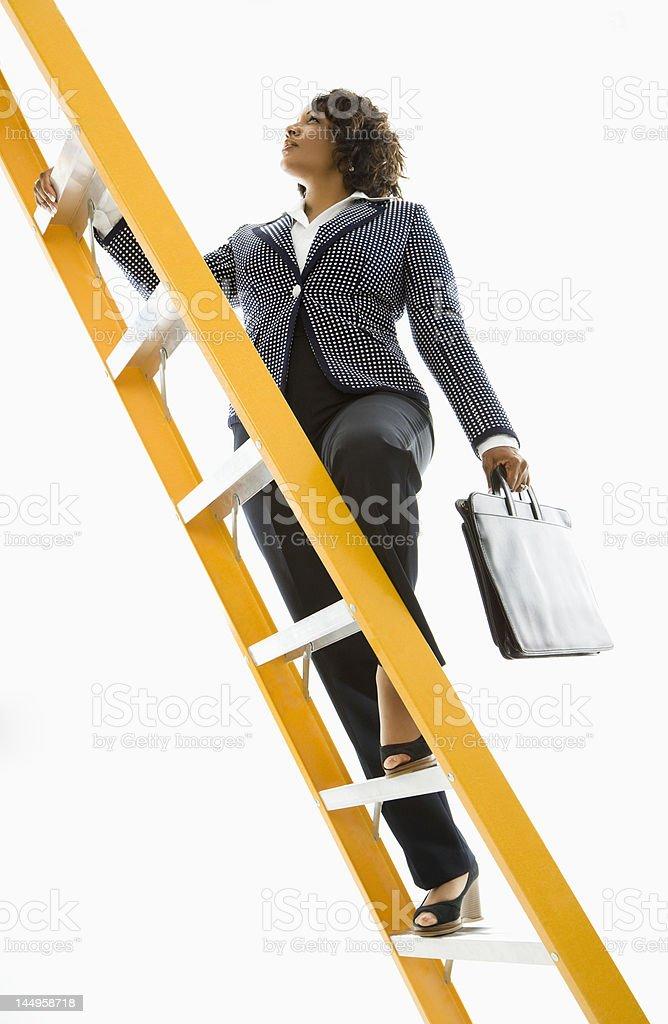 Businesswoman climbing ladder. stock photo