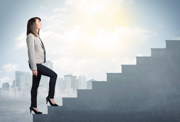 Businesswoman climbing up a concrete staircase concept Businesswoman climbing up a concrete staircase concept on city background stepping stock pictures, royalty-free photos & images